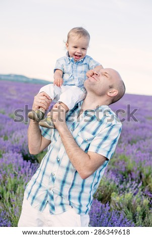 happy baby son with dad in lavender field - stock photo