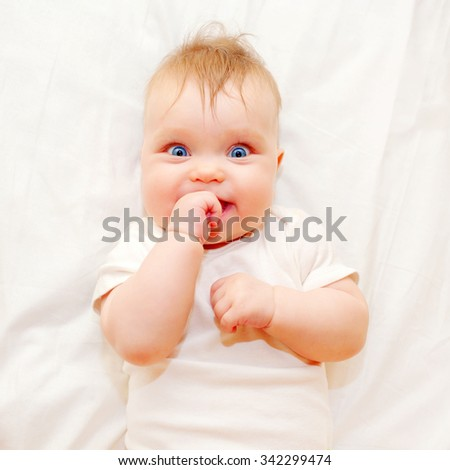 Happy baby sucking his finger on a white bed. Good morning! - stock photo