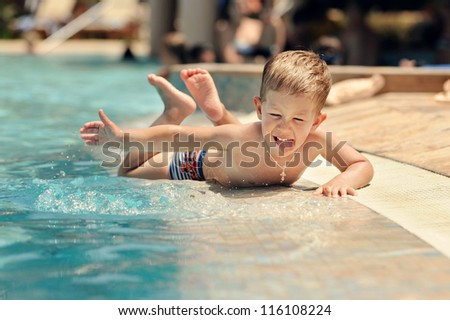 Happy baby swimming in the pool - stock photo