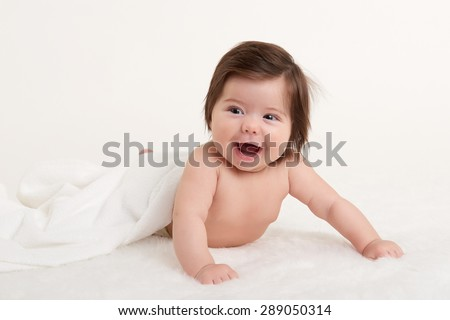 happy baby under towel on white background - stock photo