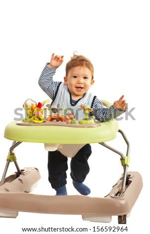 Happy baby walking in baby walker in his home - stock photo