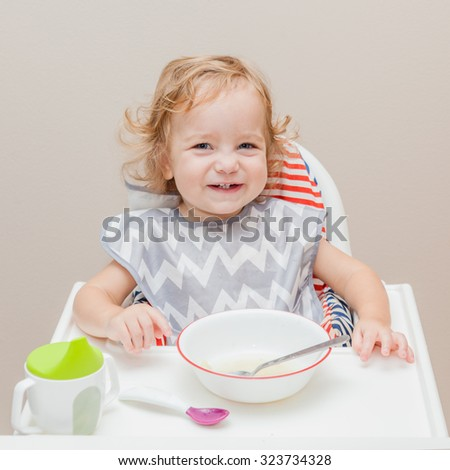 Happy baby wearing bib sitting on the child high chair with tray in the kitchen. Sipping cup, plate with soup and spoon are on the table. - stock photo