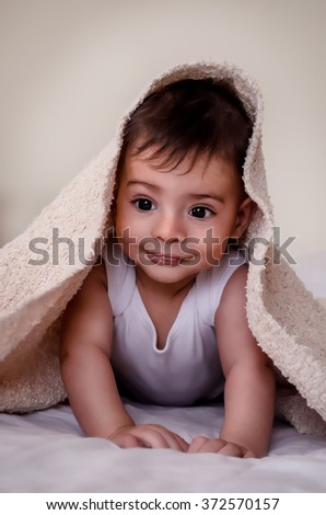happy baby with a towel after the shower in bed at home