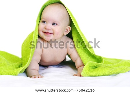Happy baby with green towel. Isolated.
