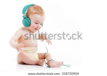 Happy baby with headphones listening to music on white background - stock photo