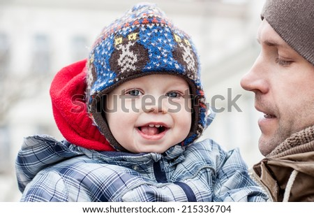 happy baby with his father outdoors in winter - stock photo