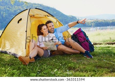 Happy backpackers sitting in tent planning their route for next days - stock photo