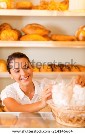 Happy baker at work. Attractive young woman in apron packing cookies and smiling while standing in bakery shop - stock photo