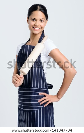 Happy baker chef in apron holding a rolling pin - stock photo