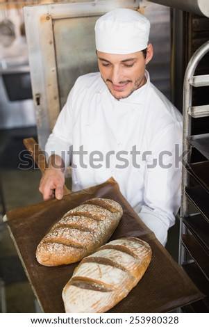 Happy baker holding tray of fresh bread in the kitchen of the bakery - stock photo