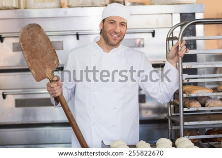 Happy baker smiling at camera in the kitchen of the bakery - stock photo