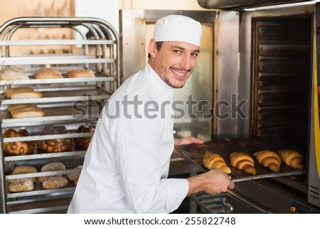 Happy baker taking out fresh croissants in the kitchen of the bakery - stock photo