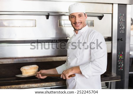 Happy baker taking out fresh loaf in the kitchen of the bakery