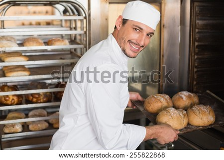 Happy baker taking out fresh loaves in the kitchen of the bakery - stock photo