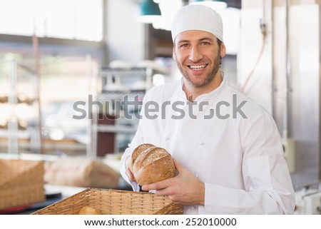 Happy baker with loaf of bread in the kitchen of the bakery - stock photo
