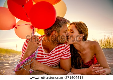 happy balloon relationship lying in sunset dawn - stock photo