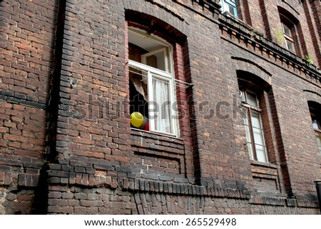 happy balloons in window frame in polish street  - stock photo
