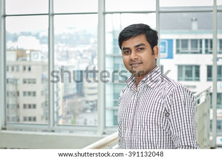 Happy bangladesh business man standing against the window - stock photo