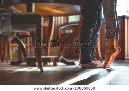 happy barefoot couple at the kitchen, girl standing on tiptoe try to kiss husband - stock photo