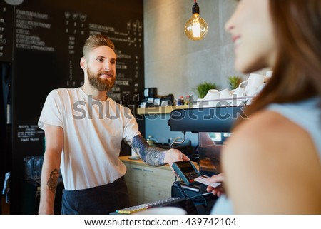 Happy barista giving payment terminal to customer at modern cafe