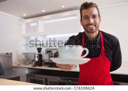 Happy barista offering cup of coffee to camera in a cafe - stock photo
