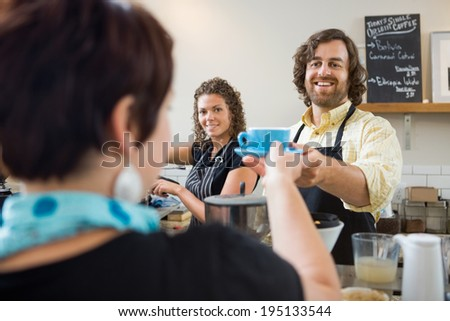 Happy barista serving customer cup of coffee - stock photo