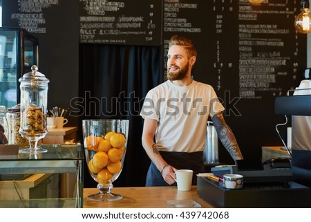 Happy barista, small business owner standing behing the counter at coffee shop