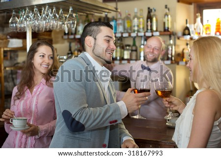 Happy bartender entertaining guests at the bar counter in bar