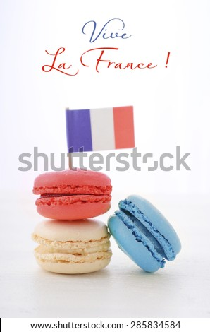 Happy Bastille Day red, white and blue macarons with French flag on white wood table with Vive La France sample text. - stock photo