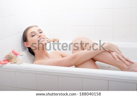 Happy bathing: smiling sexy brunette girl attractive woman enjoying taking foam spa bath with blinding eyes hugging herself bare legs smiling & looking at camera portrait - stock photo