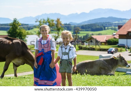 Happy Bavarian boy with sister  on the meadow with cow . Alps in background .  - stock photo