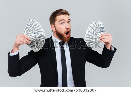 Happy bearded business man in black suit holding money in hands and looking at camera with open mouth. Isolate gray background