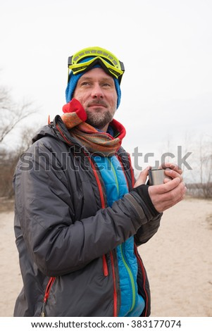 Happy bearded man, dressed as a mad pilot, drinking tea during recreation. Spring day on the coast. - stock photo