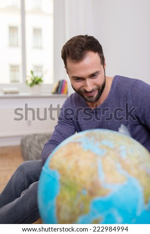 Happy bearded man planning his next vacation sitting on a sofa with a large globe looking at world destinations - stock photo