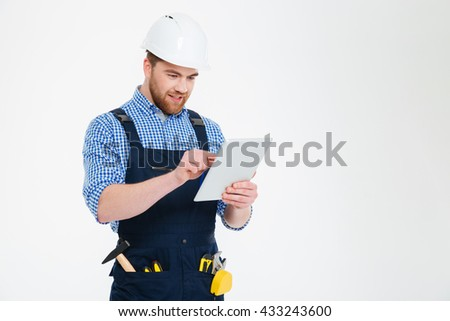 Happy bearded young builder in helmet and overall using tablet - stock photo