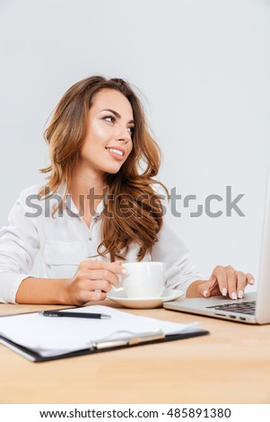 Happy beauitful young businesswoman sitting and working with laptop over white background