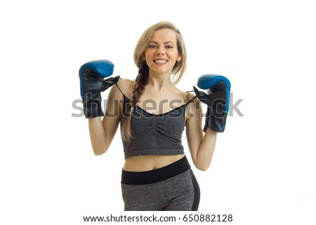 happy beautiful athletic blonde in boxing gloves looks straight and keeps hands straps from t-shirt