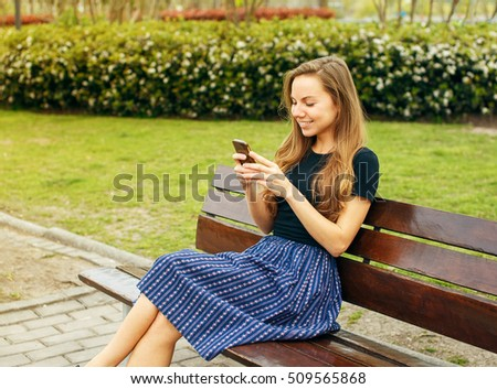 Happy beautiful blond girl sending message with her phone in the park summer day
