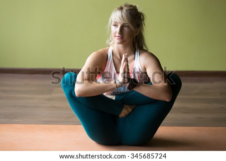 Happy beautiful blond young woman in sportswear working out indoors, doing variation of Pranama Garbha Pindasana - Womb Embryo Pose with Namaste on orange eco mat, full length - stock photo