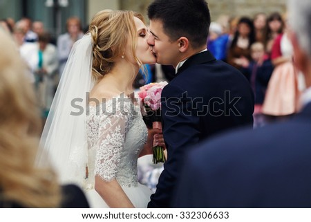 Happy beautiful blonde bride kissing handsome smiling groom close-up