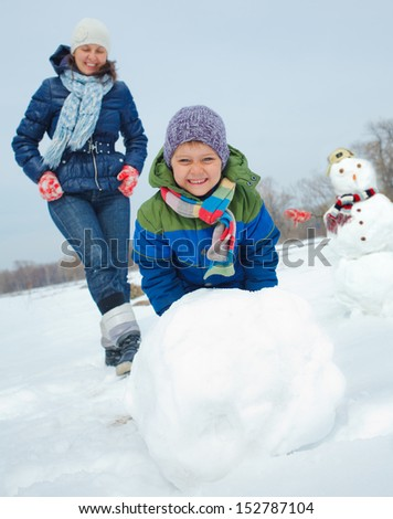 Happy beautiful boy with mother building snowman outside in winter time - stock photo