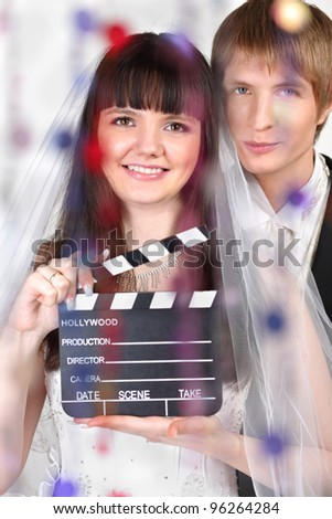 Happy beautiful bride and groom look at camera behind transparent curtain of beads; woman holds clapper board; focus on woman - stock photo