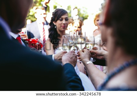 Happy beautiful bride drinking champagne at wedding reception with guests and family