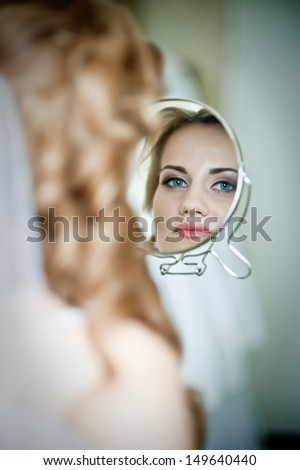 Happy beautiful bride  girl in white wedding dress with hairstyle and bright makeup at home background looking in the mirror  - stock photo