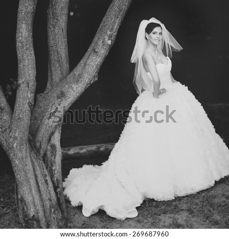 Happy beautiful brunette bride in white wedding dress with hairstyle posing in summer garden.  - stock photo