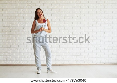 Happy beautiful brunette dressed in strip overalls, standing and holding red paper heart, white brick wall on background