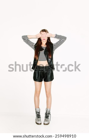 Happy beautiful brunette girl standing and covering her face with hands. Slim figure, pink lips, long hair. White background, not isolated. - stock photo