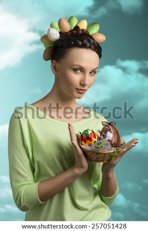 Happy, beautiful, brunette woman in spring stylisation, she has got funny hairstyle with eggs, and she is holding a little easter basket. - stock photo
