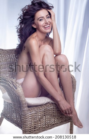 Happy beautiful brunette woman with long curly hair and amazing toothy smile sitting on chair, relaxing. - stock photo