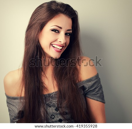 Happy beautiful brunette woman with long hair looking with toothy smiling. Toned vintage portrait - stock photo
